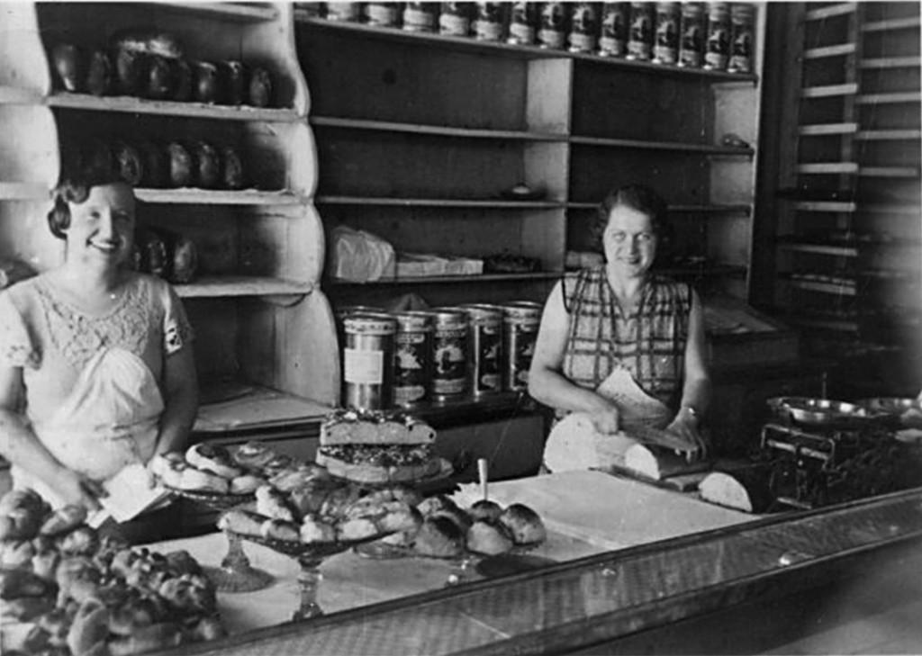 Benita Dietrich ja müüja leti taga küpsetisi välja panemas ja leiba lõikamas. (HM F 1758:9 Ff 2527); Haapsalu ja Läänemaa Muuseumid SA; Faili nimi:HMF 1758-9.jpg